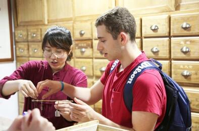 图为美国学生在体验用药秤称中药