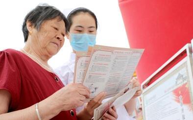 图为该院护理人员为群众分发《中医药法》宣传材料