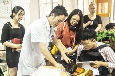图为留学生代表体验中医适宜技术治疗颈椎病