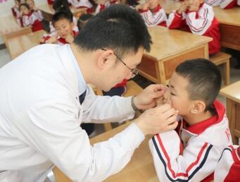 图为中医师指导学生做眼保健操