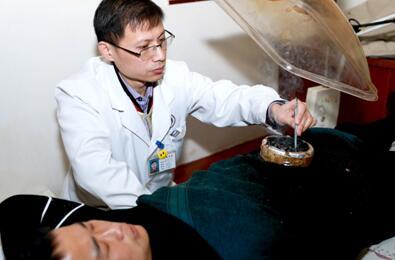 图为医务人员正在给患者进行竹筒脐灸
