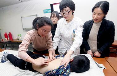 """图为""""宝妈""""们在学习小儿捏脊疗法"""