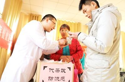 图为医务人员向社区群众发放中药防流感代茶饮