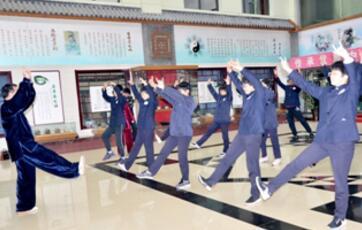 图为杨玉民带领中学生练习五禽戏