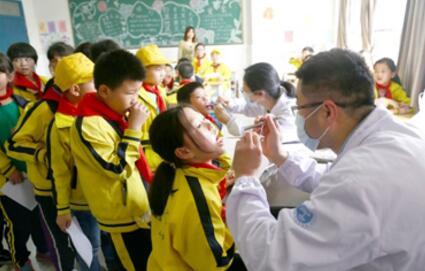 图为该院医务人员为学生体检
